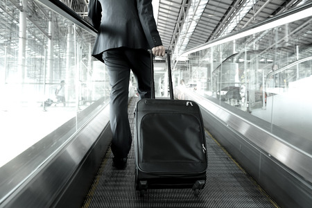 Foto de Businessman holding trolley bag going up on the escalator at the airport - Imagen libre de derechos