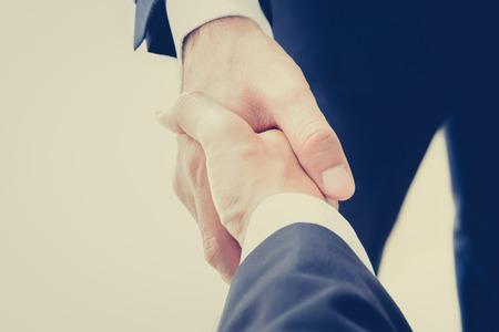 Foto de Handshake of businessmen in vintage (retro) color effect - success, congratulation, greeting & business partner concepts - Imagen libre de derechos