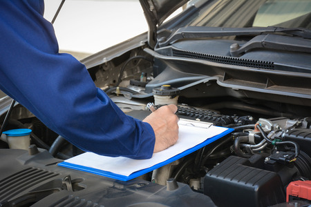 Foto de Auto mechanic (or technician) checking car engine at the garage - Imagen libre de derechos