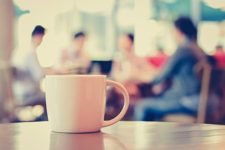 Photo pour Coffee cup on the table with people in coffee shop as blur background - vintage (retro) style color effect - image libre de droit