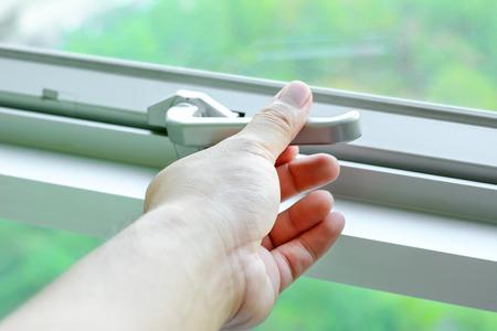 Photo pour Hand holding glass window latch handle - image libre de droit