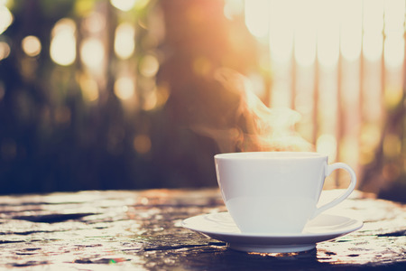 Photo pour Hot coffee on old wood table with blur background of sunlight shining through the trees - soft focus, vintage style color effect - image libre de droit