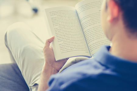 Young man reading book while sitting on the couch (over shoulder view) - vintage tone, soft focus