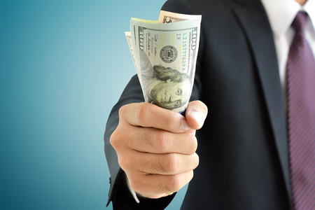 Foto de Businessman hand grabbing money, US dollar (USD) bills - Imagen libre de derechos