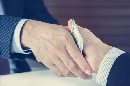 Photo for Handshake of businessmen with money, bribery concept - vintage tone - Royalty Free Image