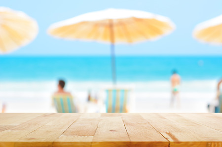 Foto de Wood table top on blurred blue sea and white sand beach background with some people - can be used for montage or display your products - Imagen libre de derechos