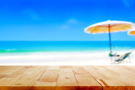 Foto de Wood table top on blurred blue sea and white sand beach background - can be used for display or montage your products - Imagen libre de derechos
