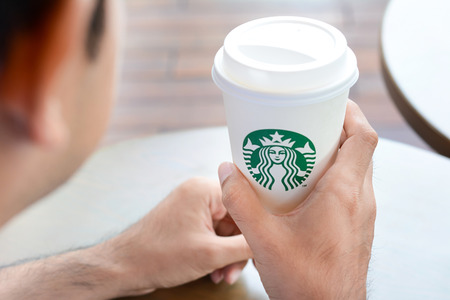 Foto de A man holding Starbucks coffee cup with brand logo. Starbucks brand is worldwide coffeehouse chains from USA. - Imagen libre de derechos
