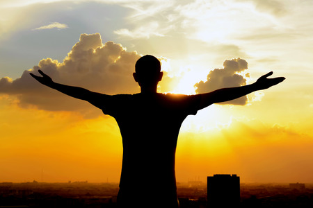 Photo pour Silhouette of a man raising his arms on  twilight sky background - happy, relaxed & success concepts - image libre de droit