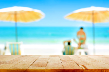 Wood table top on blurred white sand beach background with some people - can be used for montage or display your products