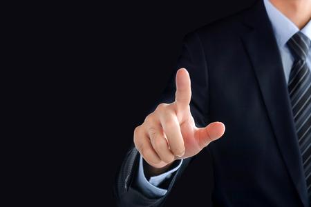 Foto de Businessman hand pointing on empty space on black background - Imagen libre de derechos