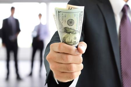 Foto de Businessman hand gripping money, US dollar (USD) bills - investment, success and profitable business concepts - Imagen libre de derechos
