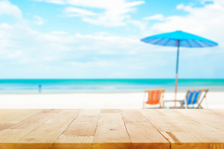 Foto de Wood table top on blur beach background with beach chairs and parasol - can be used for display or montage your products - Imagen libre de derechos