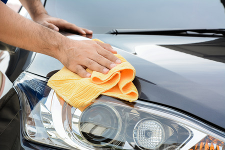 Photo pour A man cleaning car with microfiber cloth, car detailing (or valeting) concept - image libre de droit