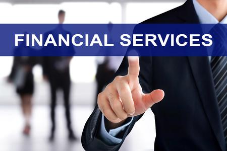 Photo pour Businessman hand touching FINANCIAL SERVICE sign on virtual screen - image libre de droit