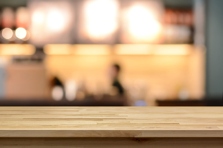 Foto de Wood table top on blur cafe ( coffee shop) interior background - can be used for display or montage your products - Imagen libre de derechos