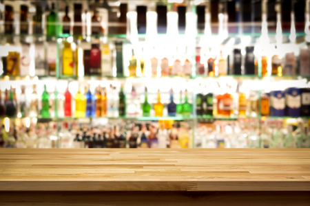 Photo for Wood bar top on blur colorful alcohol drink bottle background - Royalty Free Image