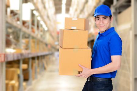 Photo pour Smiling delivery man carrying boxes on blur warehouse background - image libre de droit