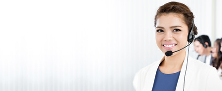 Foto de Smiling woman wearing microphone headset as an operator, telemarketer, call center and customer service staff - panoramic background or banner with blank space - Imagen libre de derechos