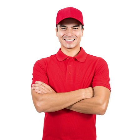 Photo for Smiling delivery man in red uniform standing with arm crossed - isolated on white background - Royalty Free Image
