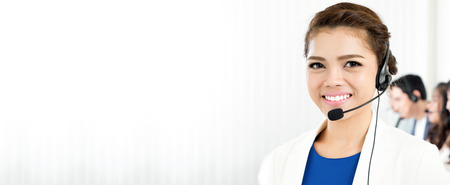 Photo pour Smiling woman wearing microphone headset as an operator, telemarketer, call center and customer service staff - panoramic background or banner with blank space - image libre de droit