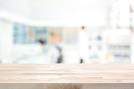 Foto de Empty wood counter top on blur pharmacy (chemist or cosmetic shop) background - Imagen libre de derechos