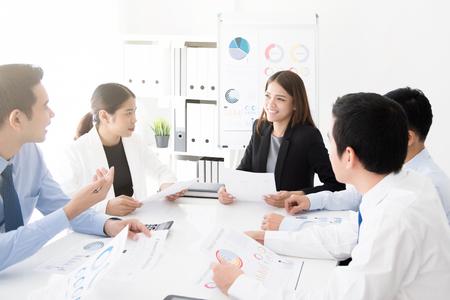 Foto de Young asian business team discussing work at meeting table in the office - Imagen libre de derechos