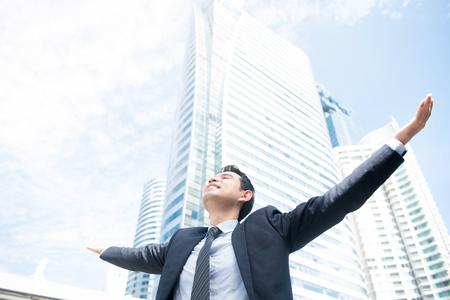 Foto de Businessman raising his arms, open palms, with face looking up to the sky - happy, success and achievement concepts - Imagen libre de derechos
