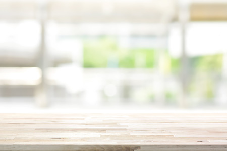 Foto de Wood table top on blur kitchen window background - can be used for display or montage your products (foods) - Imagen libre de derechos