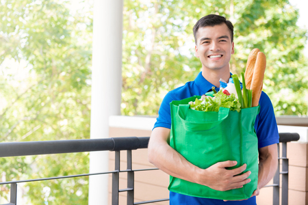 Foto de Smiling delivery man holding recycle grocery shopping bag with food inside - Imagen libre de derechos
