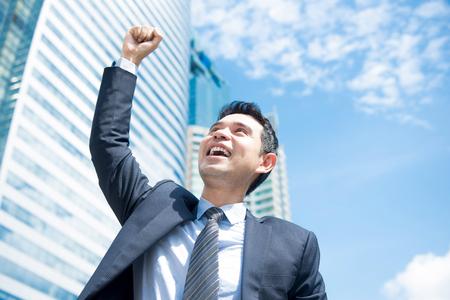 Photo pour Businessman smiling and raising his fist in the air in office building background - business success and achievement concepts - image libre de droit