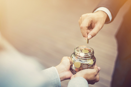 Photo pour Businessman hand putting money (coin) in the glass jar held by a woman, vintage tone effect - image libre de droit