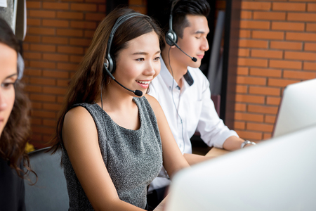 Photo pour Smiling Asian businesswoman working in call center as  an operator or telemarketer - image libre de droit