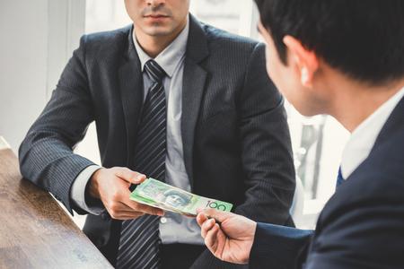 Foto de Businessman giving money, Australian dollars, to his partner - bribery and corruption concepts - Imagen libre de derechos