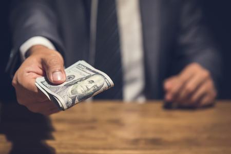 Foto de Dishonest businessman secretly giving away money in the dark - bribery, scam and venality concepts - Imagen libre de derechos