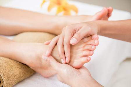 Photo pour Professional therapist giving relaxing reflexology foot massage to a woman in spa - image libre de droit