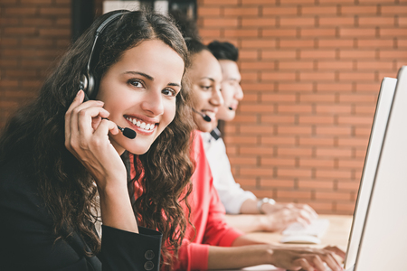 Foto de Smiling beautiful woman telemarketing customer service agent working in call center office with her multiethnic team - Imagen libre de derechos