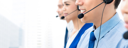 Photo pour Call center agents talking on the phone to customers with a friendly and helpful attitude - panoramic banner with copy space - image libre de droit