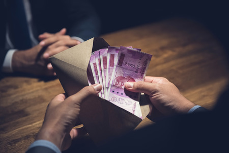 Photo for Businessman counting money, Indian Rupee currency, in the envelope just given by his partner after making an agreement in private dark room - loan, briberry and corruption scam concepts - Royalty Free Image