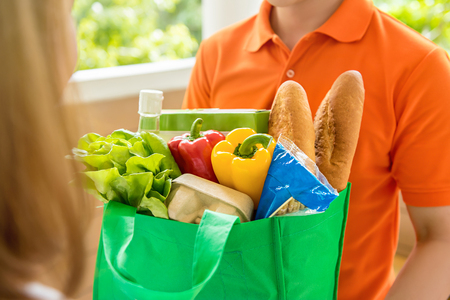 Photo pour Grocery store delivey man wearing orange polo-shirt delivering food to a woman at home - image libre de droit