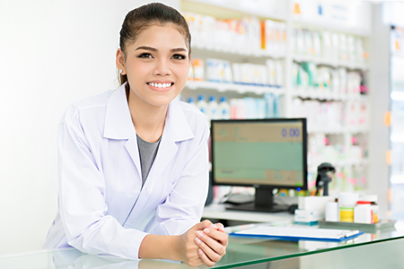 Foto de Smiling beautiful young Asian woman pharmacist in white gown coat at the counter in pharmacy (chemist shop or drugstore) - Imagen libre de derechos