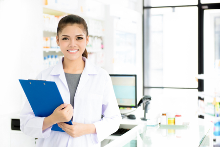 Photo for Smiling beautiful young Asian woman pharmacist in white gown coat at working in pharmacy (chemist shop or drugstore) - Royalty Free Image