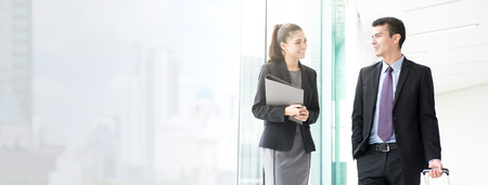 Foto de Asian businesswoman talking with a male colleague while walking in the building corridor (or airport terminal ) - panoramic web banner with copy space - Imagen libre de derechos