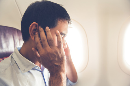 Foto de Male passenger having ear pop on the airplane while taking off (or landing) - Imagen libre de derechos