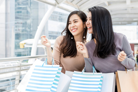 Foto de Beautiful young Asian woman friends enjoying traveling and shopping in the city during summer holiday sales season - Imagen libre de derechos