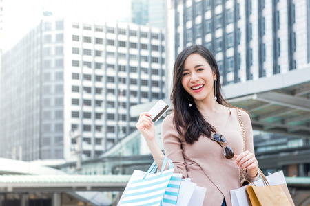 Photo pour Beautiful young smiling Asian woman carrying shopping bags in her arms presenting credit card that just used for making payment - image libre de droit