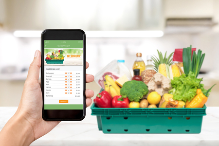 Photo pour Grocery online shopping application on smartphone screen with food at home in background - image libre de droit
