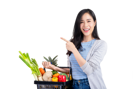 Photo for Beautiful Asian woman holding shopping basket full of vegetables and groceries, studio shot isolated on white background - Royalty Free Image