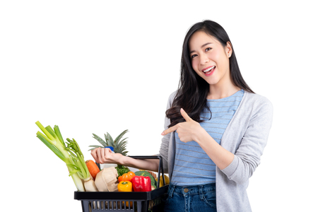 Photo pour Beautiful Asian woman holding shopping basket full of vegetables and groceries, studio shot isolated on white background - image libre de droit