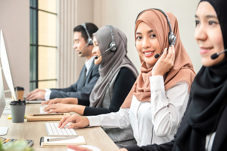 Photo pour Friendly beautiful Asian muslim woman wearing microphone headset working as customer support operator with team in call center office - image libre de droit